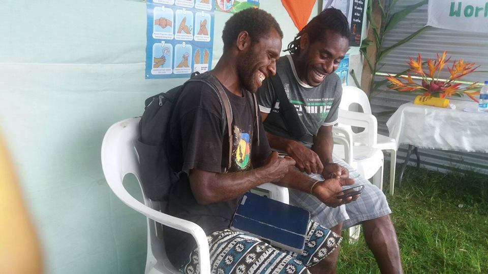 Photo of two ni-Vanuatu youth boys on the remote island of Tanna playing Rispek Danis (The Respect Dance) a serious video game about consent.